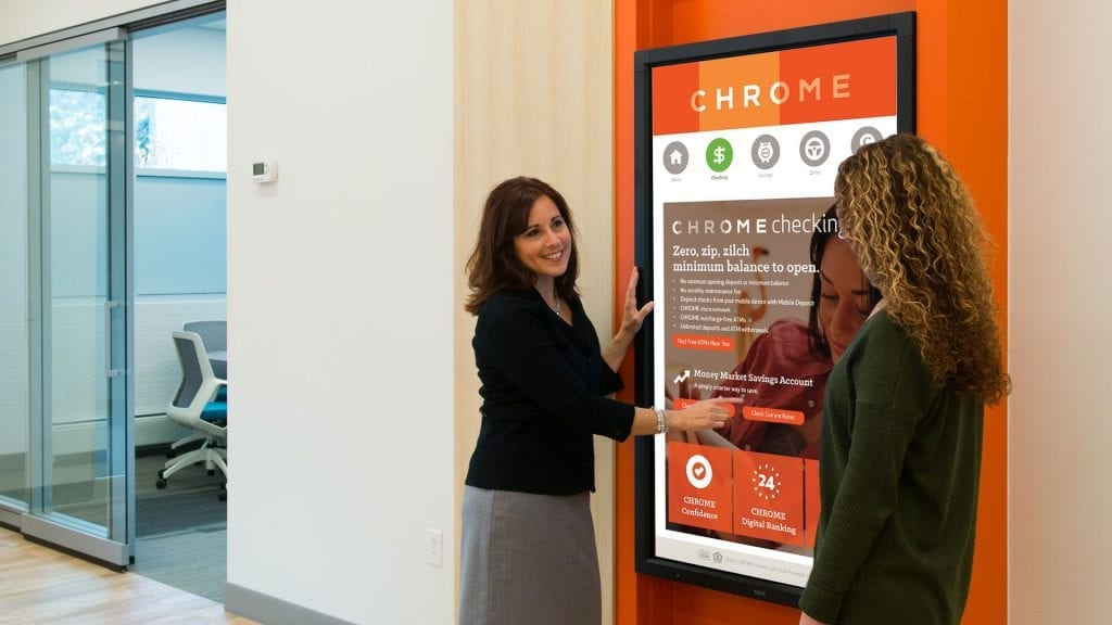 Bank representative showing a customer how to use the touch banking kiosk